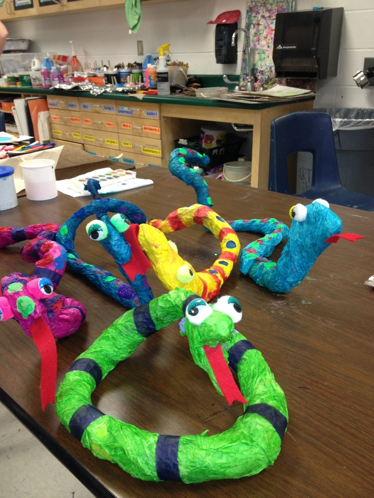3-D wire hanger snakes done with newspaper, tissue paper, goggle eyes and Staflo liquid starch to hold the tissue paper on.