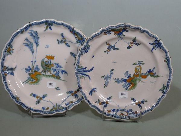 MARSEILLE Atelier de LEROY  Deux assiettes à bordure contournée, à décor polychrome de grotesques (chinois et joueur de harpe) dans des paysages fleuris.  18ème siècle.  D : 24 cm.