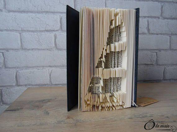 La collection A Livre Ouvert est une série de livres doccasion transformés en objets de décoration via plusieurs techniques (découpage, pliage ou décou-pliage). Chaque page est découpée et/ou pliée à la main pour donner vie à un motif.  Le modèle Dans les vagues est un livre découpé et plié pour représenter la silhouette dun voilier. Le livre possède une magnifique couverture bleue et or sur le thème de la mer. VENDU SEUL