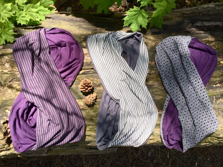 Purple and grey infinity scarves nestled amongst pine cones and maple leaves.