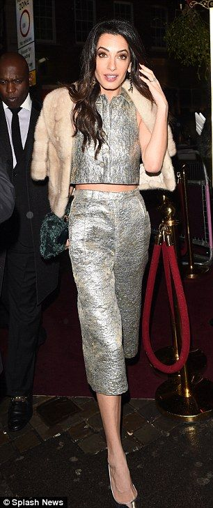 Amal looked chic as she displayed her trim figure in a silver crop top and culottes...