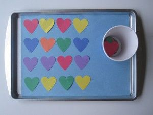 paper hearts, a cookie sheet, double stick tape , a paper cup