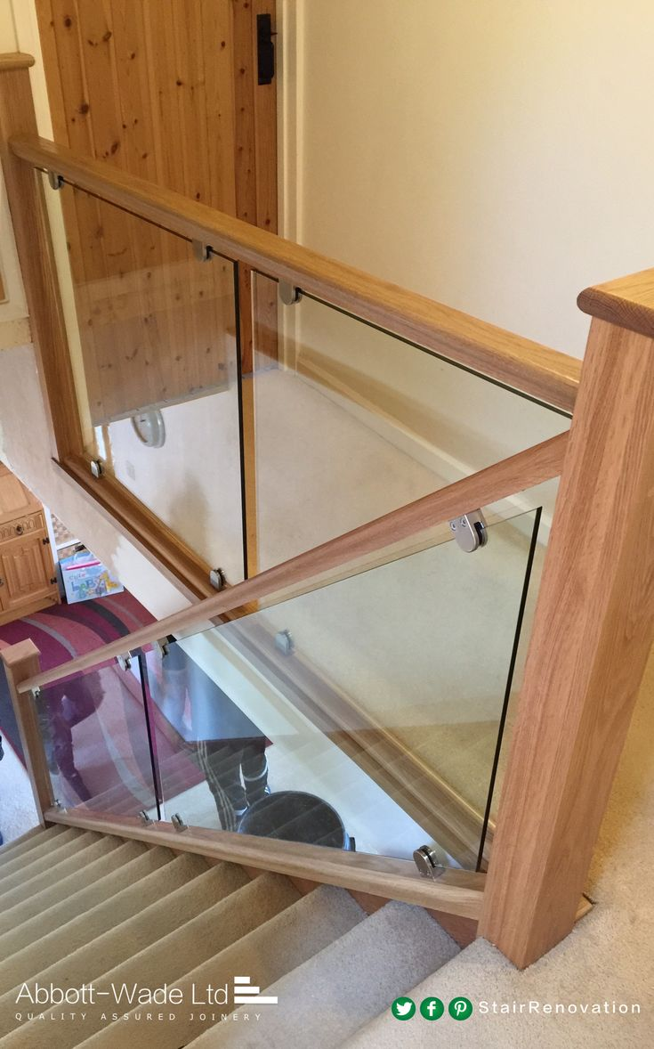 An Abbott-Wade oak staircase with glass balustrade installed on brackets.