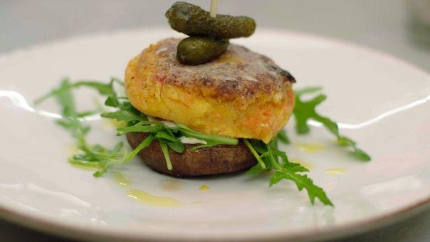 Eén - Dagelijkse kost - Groenteburgers met portobello600 g aardappelen (loskokend) 400 g knolselders 1⁄2 butternut (of een stuk klassieke pompoen) 2 dikke wortels 2 stengels selder 2 teentjes look 1⁄2 rode chilipeper 1 takje rozemarijn 4 takjes tijm scheutje olijfolie evt. een snuifje komijnpoeder  4 eetlepels maïszetmeel (bv. Maïzena) peper zout Voor de garnituren 8 portobello-paddenstoelen 1 teentje look een flinke scheut olijfolie peper zout Om af te werken 100 g rucolla, augurken