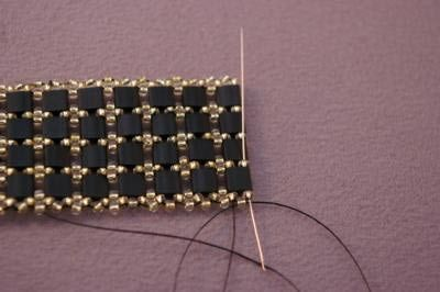 To add the clasp, pass needle through beads until you are exiting one of the seed beads between Tila beads.