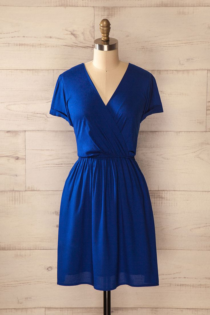 Le feu de camp crépitait doucement au son des rires des campeurs.  The camp fire slowly crackled at the sound of the campers' laughs. Blue wrap dress with short sleeves and pockets https://1861.ca/products/mochlos