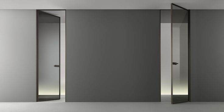 the flush door Zen. Brown aluminum structure and transparent gray glass, handle with magnetic lock and revolving plug.