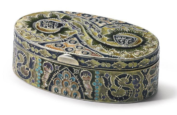 A FABERGÉ GILDED SILVER AND CLOISONNÉ ENAMEL BOX, MOSCOW, 1908-1917 oval with hinged lid, enameled with abstract and foliate ornament in olive green, navy blue, turquoise, peach, and amethyst, the decoration enhanced with applied silver cloisons, struck K. Fabergé in Cyrillic beneath Imperial warrant overstriking Cyrillic initials of Fedor Rückert, 88 standard, and scratched number 27623 width 2 5/16 in., 5.9 cm