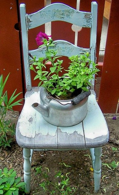 Beautiful! Distressed old chair as garden decor with a beautiful, #upcycle kitchen ware as a planter resting on it.
