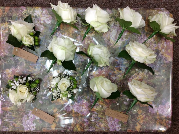 Cream rose buttonholes neatly packaged with people's name tags - with ladies corsages to match
