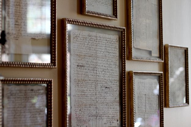 old family letters framed in gold leaf and floating between the glass