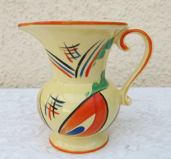Collectable Art Deco Abstract Pattern Jug by Ditmar Urbach, Czechoslavakia. Vibrantly painted in oranges, green, blue and black over a yellow body in a fabulous abstract pattern, that just screams Art Deco!  The factory which made this jug has a really interesting history, in 1913, the factory was purchased by Triptis A.G and became an independent factory but was confiscated by the newly founded state of Czechoslovakia in 1919 and operated as Ditmar-Urbach, under its previous owner, Richard…
