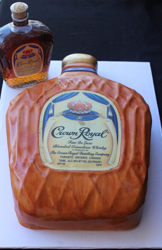 Groom's Cakes - The groom loves Crown Royal almost as much as his bride!  The traditional Red Velvet with cream cheese covered with fondant and hand painted.  The label is an edible image.