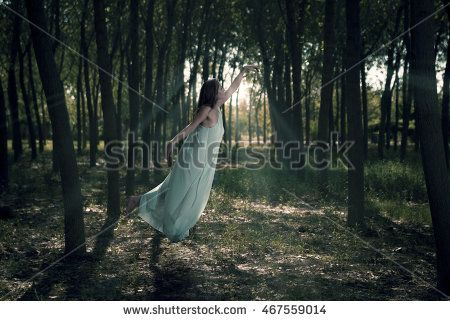 Aqua blue dressed woman flying in the woods.