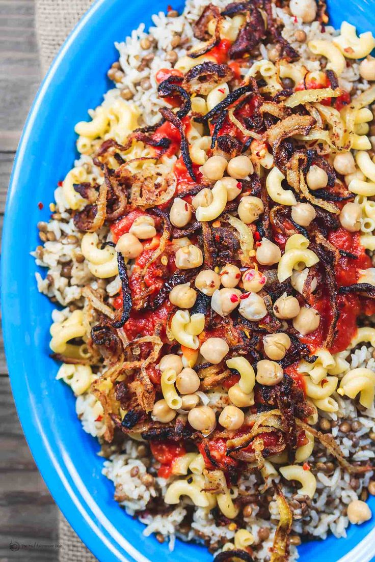 All star koshari recipe! Comforting bowl of lentils and rice, pasta, and chickpeas smothered in a spiced tomato sauce and topped w/ crispy thin onion rings!