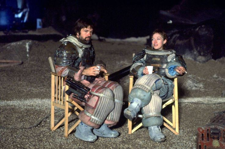 Tom Skerritt and Veronica Cartwright take a well deserved break during filming of the Alien while wearing the infamous spacesuit costumes.