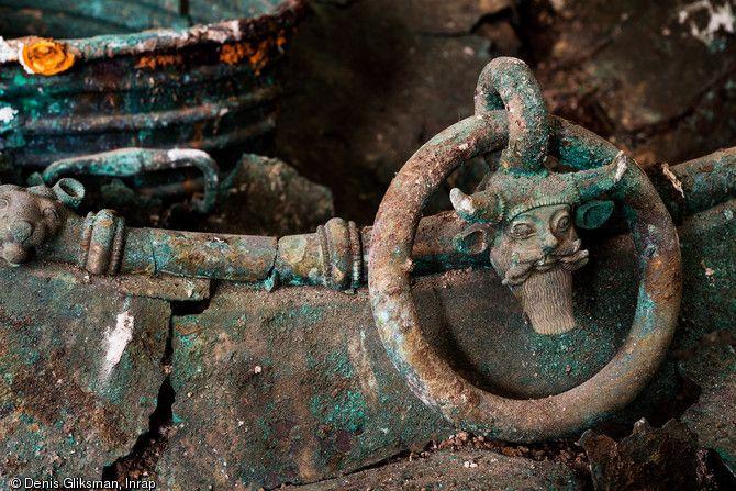 Vue de détail des anses d'un chaudron  au décor figurant le dieu-fleuve Acheloos, trouvé dans un complexe funéraire daté du Ve s. avant notre ère à Lavau (Aube) en 2015. À l'arrière plan une ciste (seau) en bronze.