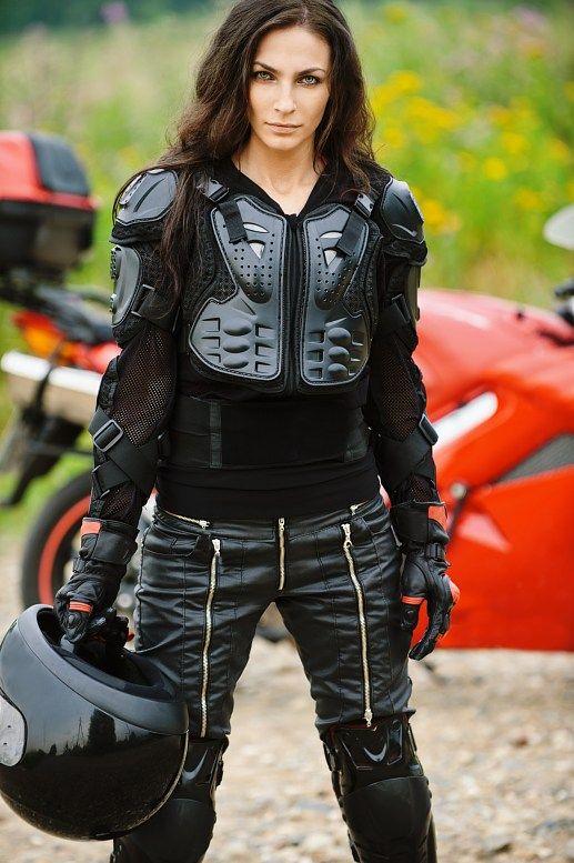Una joven rusa ataviadas con los trajes de protección y manteniendo en pie el casco en contra de su motocicleta roja