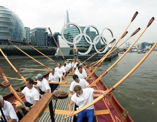 The royal barge Gloriana carries the Olympic flame along the river Thames on the final day of the Olympic torch relay, July 27, 2012, in London. (Yui Mok/LOCOG/AP Photo)