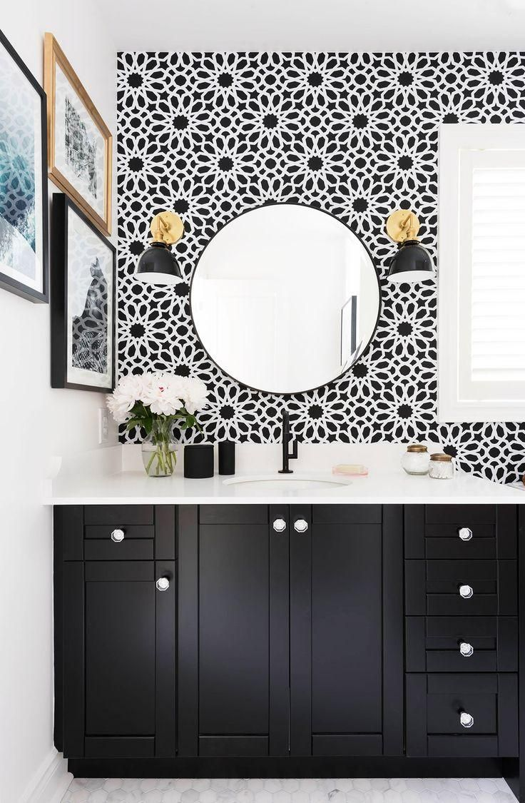 Stunning and affordable black and white bathroom makeover remodel project with touches of brass, Spanish-inspired geometric patterned black and white tile, traditional cabinets, marble counter top, gallery wall, and brass tipped wall mounted sconces. Love!