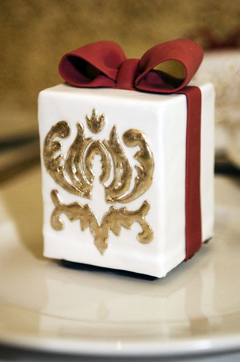 An individual cake is decorated in gold and topped with a red fondant bow. #WeddingCake