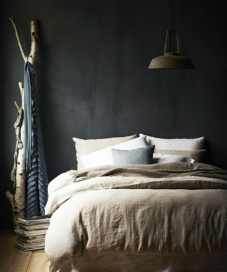 An oasis for sleep with rich dark walls, natural colored linens and rustic accents in wood and metal.