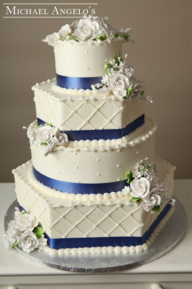 Royal Blue & White Roses #30Ribbons This four-tier hexagon and round buttercream cake is accented with white gum paste flowers as a topper and side accents. Each layer is wrapped with a royal blue ribbon and dots and lace.