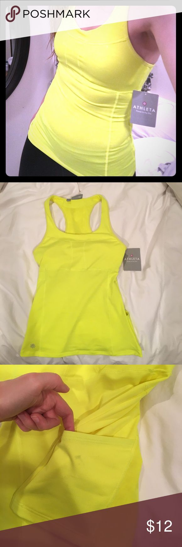 Athleta Neon Yellow workout tank This is a reposh. I needed a bright neon yellow workout top for running/biking in the city. This would have been perfect but it's much more of an XXS fit than a XS. I'm about a 34B and I think a 32 bust would find it more comfortable. It still has tags attached. I did notice some discoloration when I received it- but it's never been through the wash, so that might remove them. It has pockets on the back hem and has a built in shelf bra. Athleta Tops Tank Tops