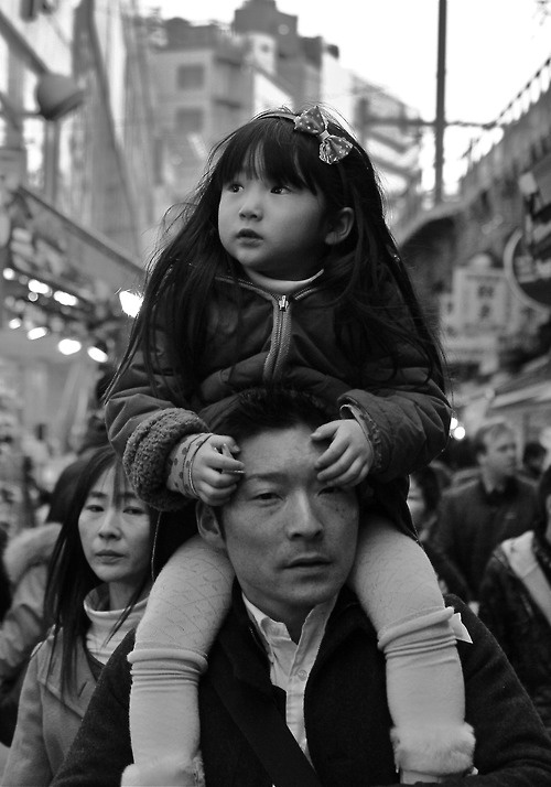 Photo by Motographer in Japan - Tokyo. Young Japanese girl carried by her father. Undated vintage black and white.