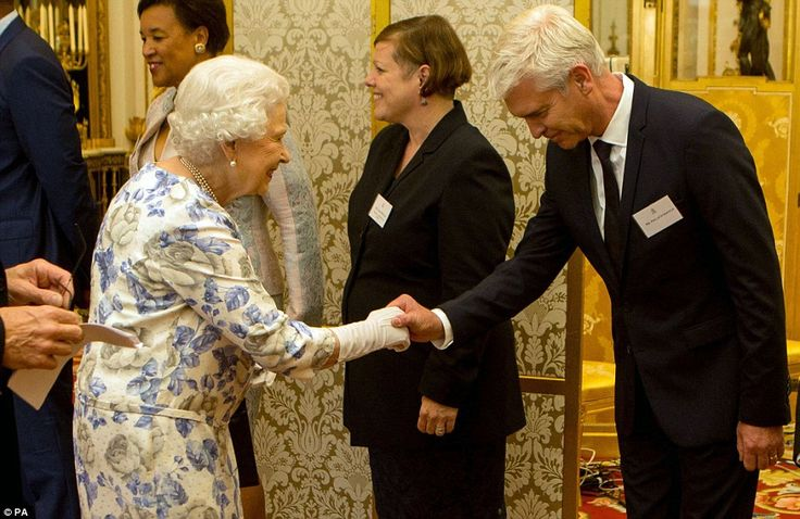 Phillip Schofield bows as he meets the Queen at the ceremony to honour young people from 45 countries across the Commonwealth