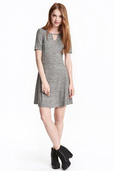 Трикотажное платье: Короткое платье из фактурного трикотажа. На платье сверху декоративный вырез, отрезное по талии, юбка широкая.