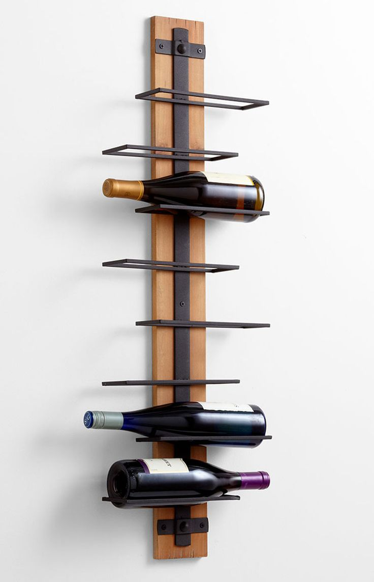 13 Wine Bottle Storage Ideas For Your Stylish Home // this wall mounted wine rack lets you make use of extra space on your walls but has the added bonus of letting you see exactly which wine you're grabbing without having to pull them all out.