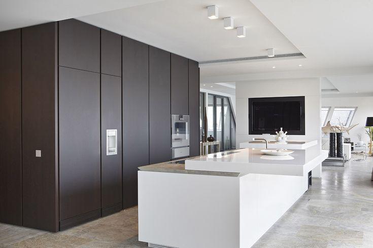 """Semplici volumi diventano elementi funzionali: così è stato progettato un attico di Amsterdam, in cui la cucina su misura si annulla con un """"touch""""."""
