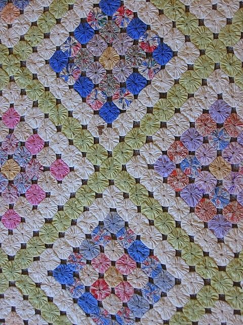 Love this yoyo quilt pattern: granny squares with alternating contracting yoyo's. Block borders in white and light green sash. Beautiful.