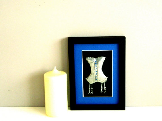 A metal art sculpture pewter embossed corset with suspenders trimmed with Capri Blue Swarovski crystals. A black frame and royal blue mountboard complete this framed metal sculpture.