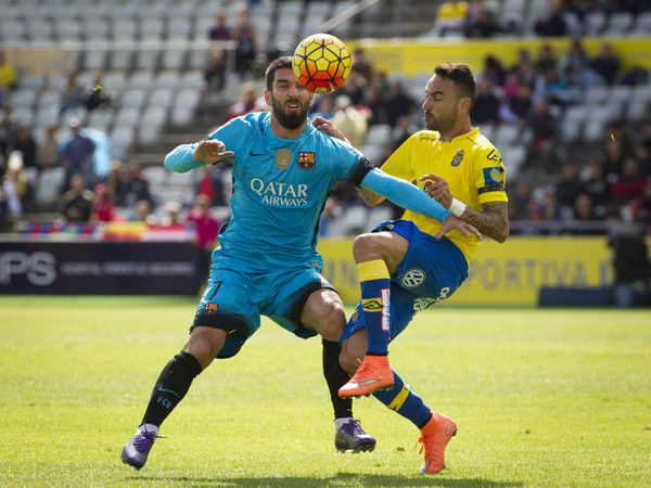 Barcelona's Turkish midfielder Arda Turan (L) vies with Las Palmas' midfielder Momo during the Spanish league football match UD Las Palmas vs FC Barcelona at the Gran Canaria stadium in Las Palmas de Gran Canaria on February 20, 2016.