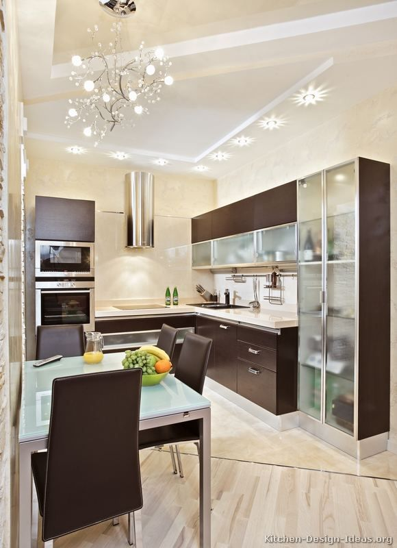 """""""Kitchen of the Day"""" -- A Small Kitchen Design with Modern Wood Cabinets: With essential cooking appliances in close proximity, this small kitchen design has dark wood cabinets, dramatic lighting, and space saving features."""