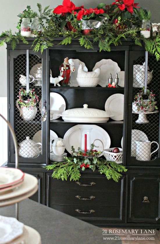 Hutch painted black, center doors removed, displays white ironstone and Christmas decor.