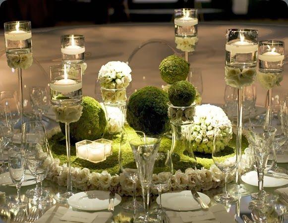 Miękki mech, świeże kwiaty i blask świec - dekoracja ślubna sali przyjęć