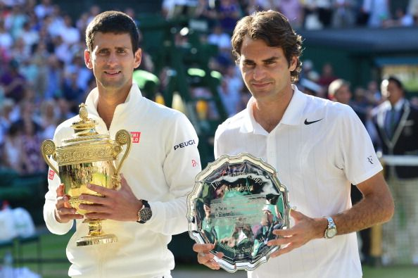 Winner Serbia's Novak Djokovic (L) and runner-up Switzerland's Roger Federer hold their trophies during the presentation at the end of their men's singles final match on day thirteen of the 2014 Wimbledon Championships at The All England Tennis Club in Wimbledon, southwest London, on July 6, 2014