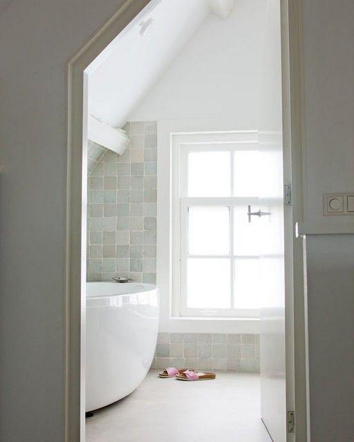 Prachtige natuurlijke tegels in de badkamer met verder veel wit.