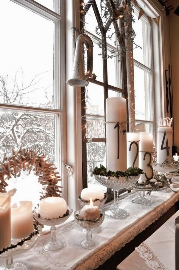 Beautiful Advent candle vignette on a window sill bright with white candles and crystal.