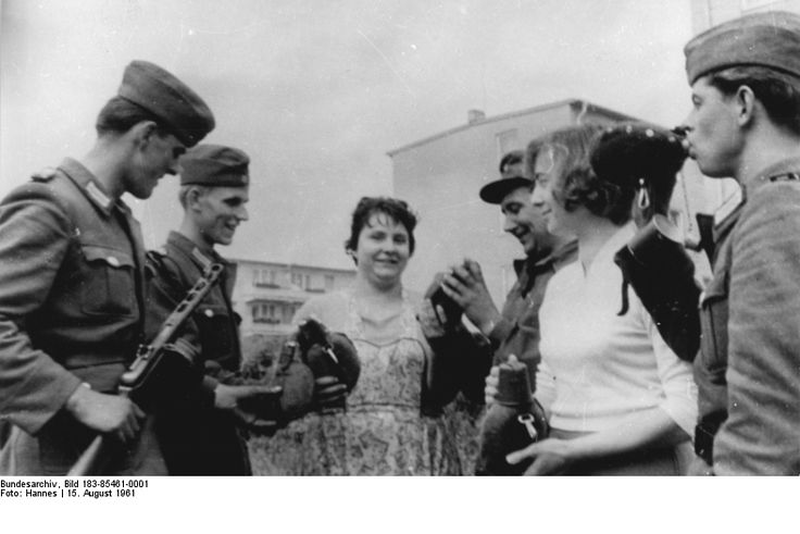"""""""Die Berliner Bevölkerung fühlt sich mit den bewaffneten Kräften eng verbunden, die zur Sicherung des Friedens in der Hauptstadt der DDR ihren Dienst tun. Auf unserem Foto verteilen die Arbeiterinnen Erfrischungen."""", 15. August 1961. (© Bundesarchiv, Bild 183-85461-0001, Foto: ADN/ZB, Hannes)"""