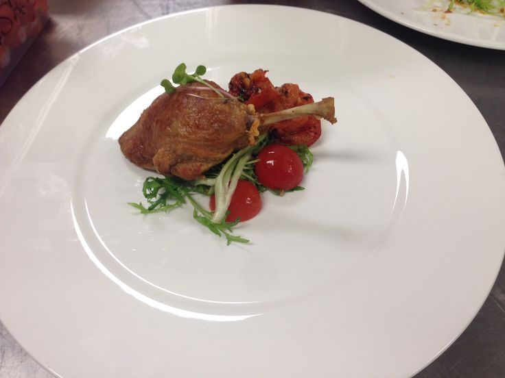 Duck confit, curly endive in hazelnut dressing, roasted Roma tomatoes, duck jus reduction
