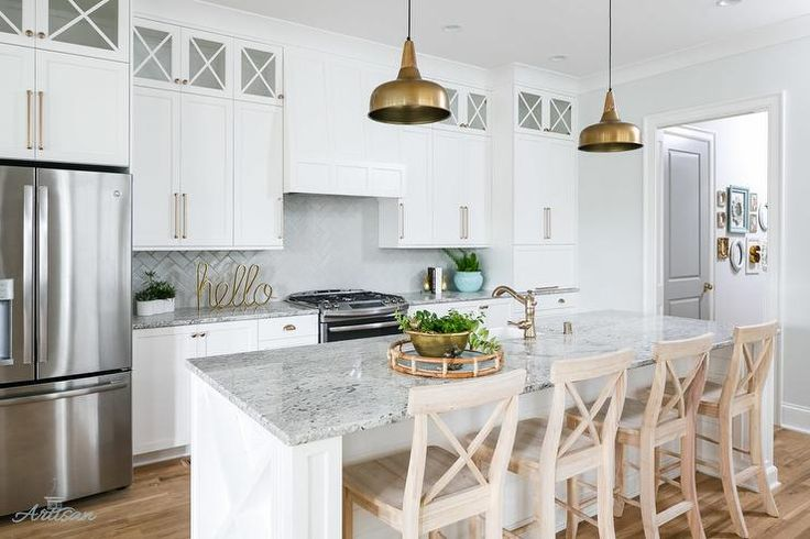 White transitional kitchen with gold accents with styled with four light wood x-back bar stools positioned in front of a gray granite countertop accenting a white shiplap center island finished with sink and satin nickel faucet lit by two gold lanterns.