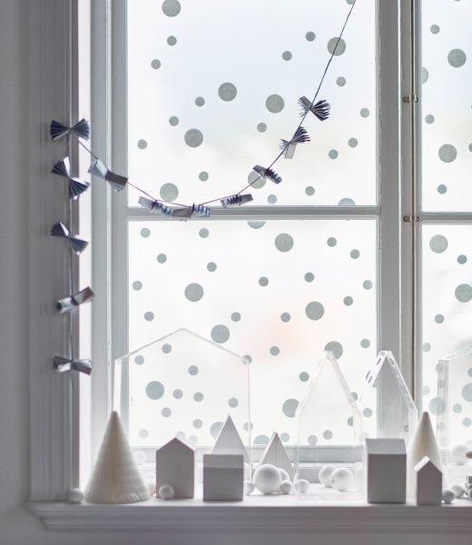 Okno ozdobené jednoduchou zimnou rozprávkovou krajinou z malých papierových domčekov, stromov a snehových vločiek.
