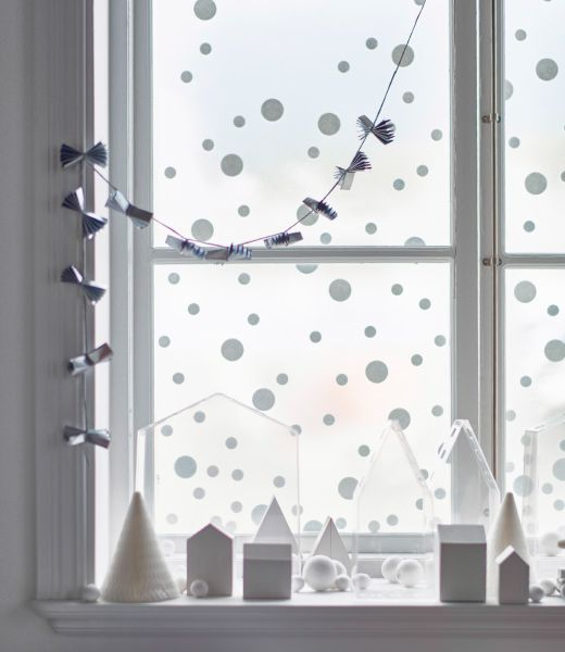 A window is decorated with an easy winter wonderland landscape, made with small paper houses, trees, and snowflakes.