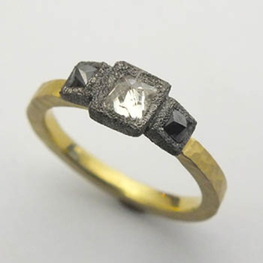 TODD POWNELL - 18k Yellow Gold ring with inverse set Princess cut center diamond, and two Princess cut black diamonds on a 2mm 18k yellow gold hammered shank.