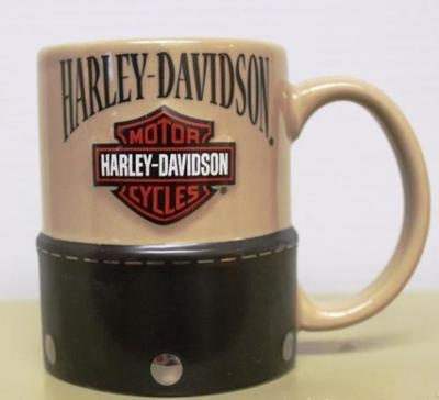 """This awesome mug is the perfect gift for any Harley & coffee lover.    The bottom portion of this ceramic piece features a black """"saddle bag""""   with detailed silver stitching and studs.    The top portion of the mug comes in camel with beautiful graphics   of the Harley logo."""