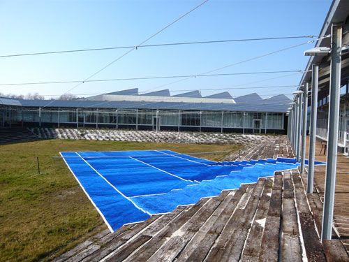 """Laurent Perbos, 2008, Aire. """"Gazon synthétique, filet de tennis Dimensions réglementaires d'un court de tennis soit 23,774 x 10,973 m Vue de l'exposition à La Winery de Philipe Raoux, Castelnau-en-Médoc."""" Caption from link"""